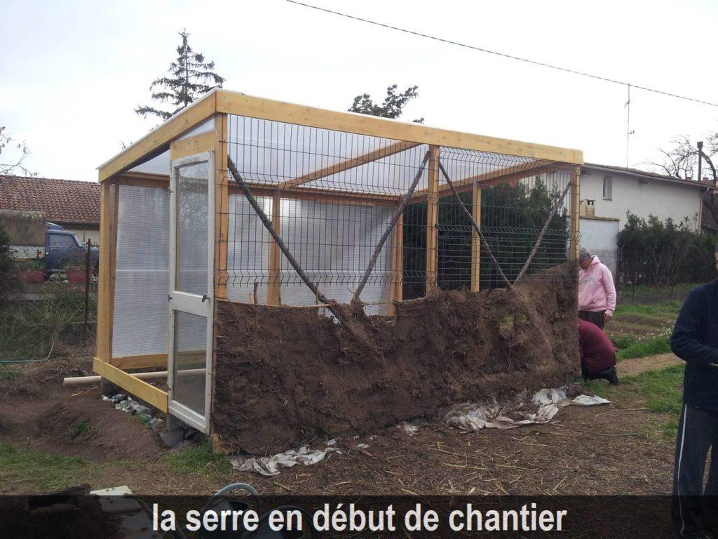 photo d'une serre bioclimatique en début de chantier, mur en torchis en cours de réalisation