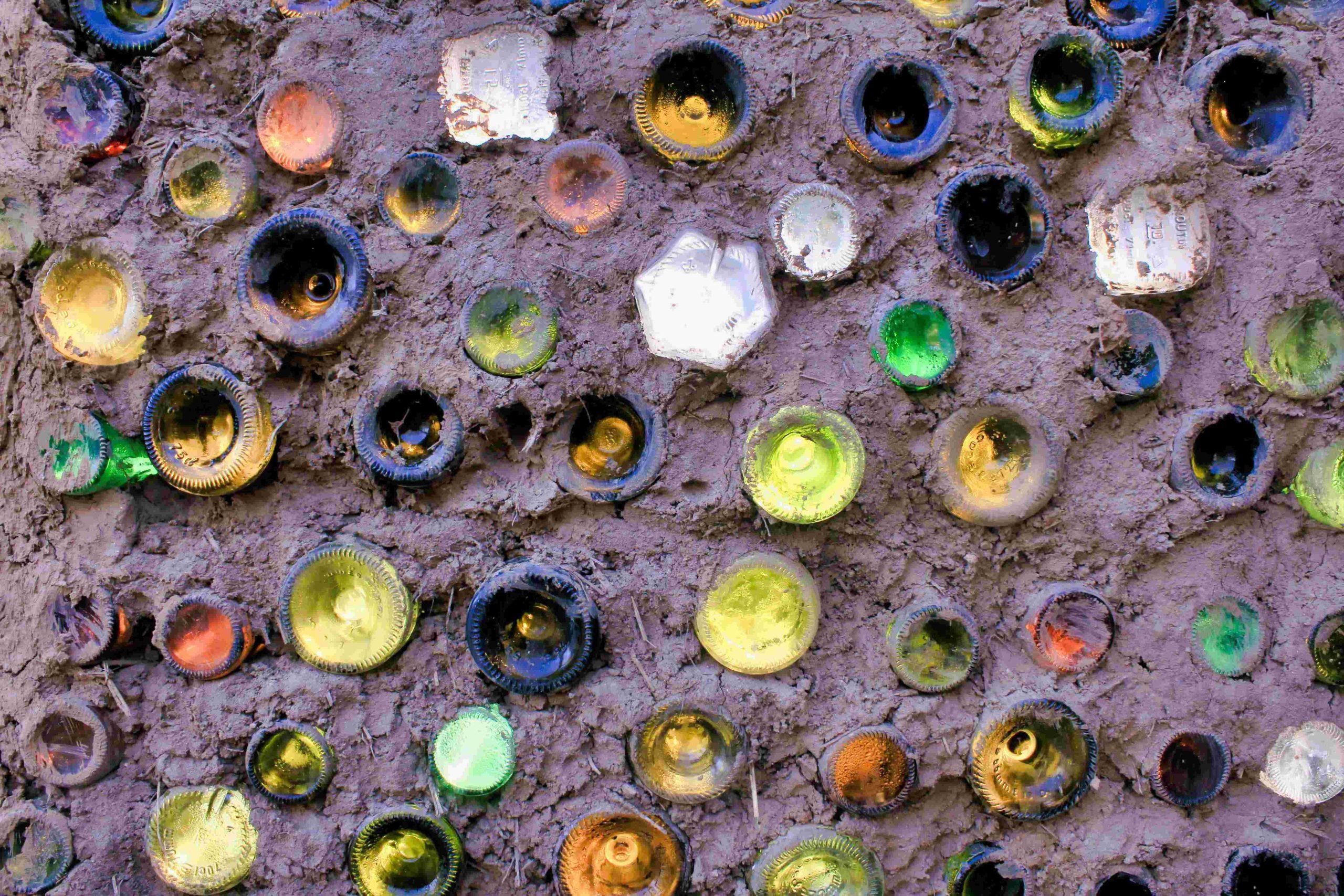 un mur en bouteilles de verre fait maison avec des bouteilles de récupération de plusieurs couleurs et tailles