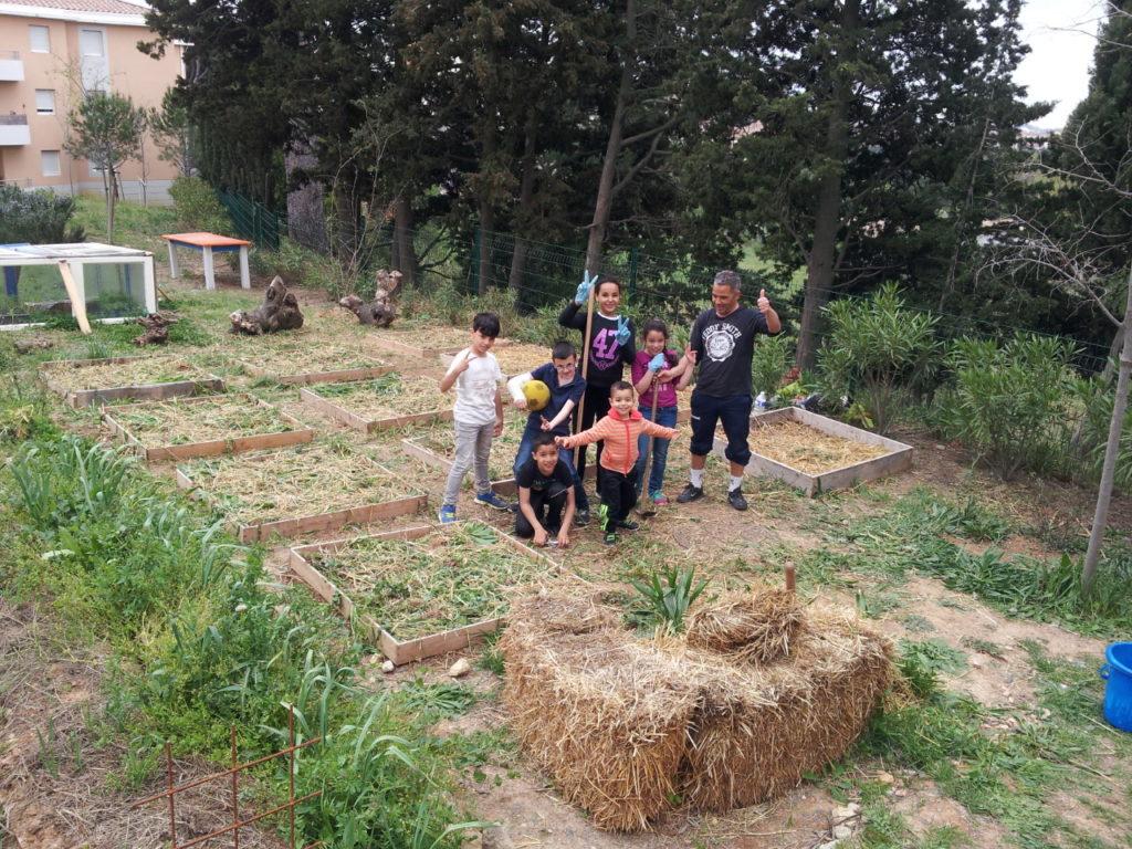 un groupe d'enfants accompagnés d'un adulte posent pour la photo, dans un jardin partagé