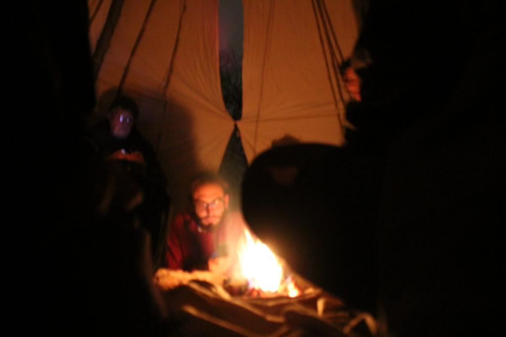 un homme prend la parole autour du feu, dans un tippi pour un cercle de paroles