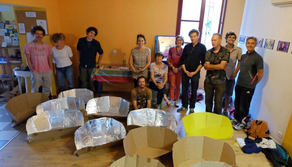 dix personnes posent avec leur four solaire juste fabriqué lors d'un atelier associatif