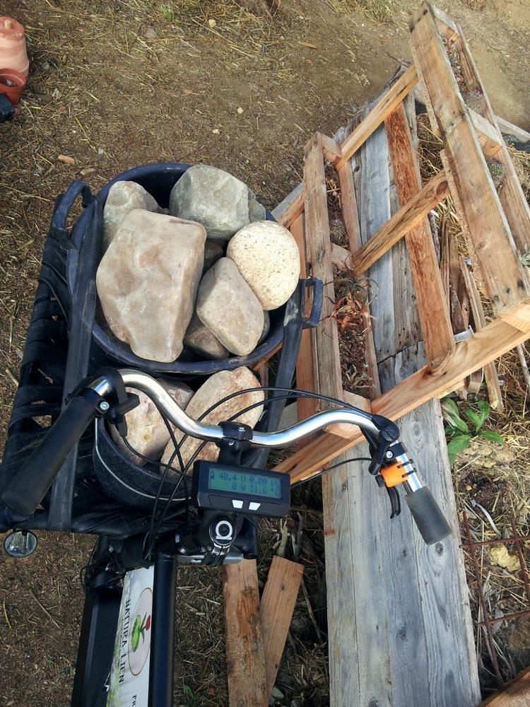 de lourds cailloux transportés sur la plate forme avant d'un vélo cargo