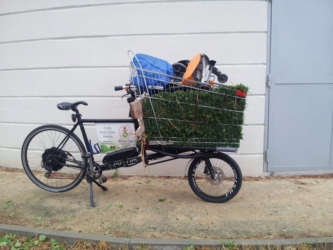vélo cargo transportant une tondeuse manuelle et de la tonte de gazon