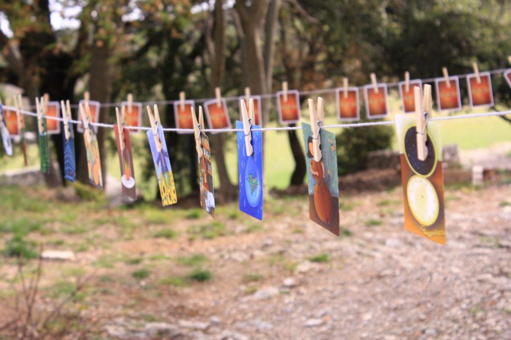 des cartes du jeu Dixit accrochées sur une ficelle avec des pinces à linge