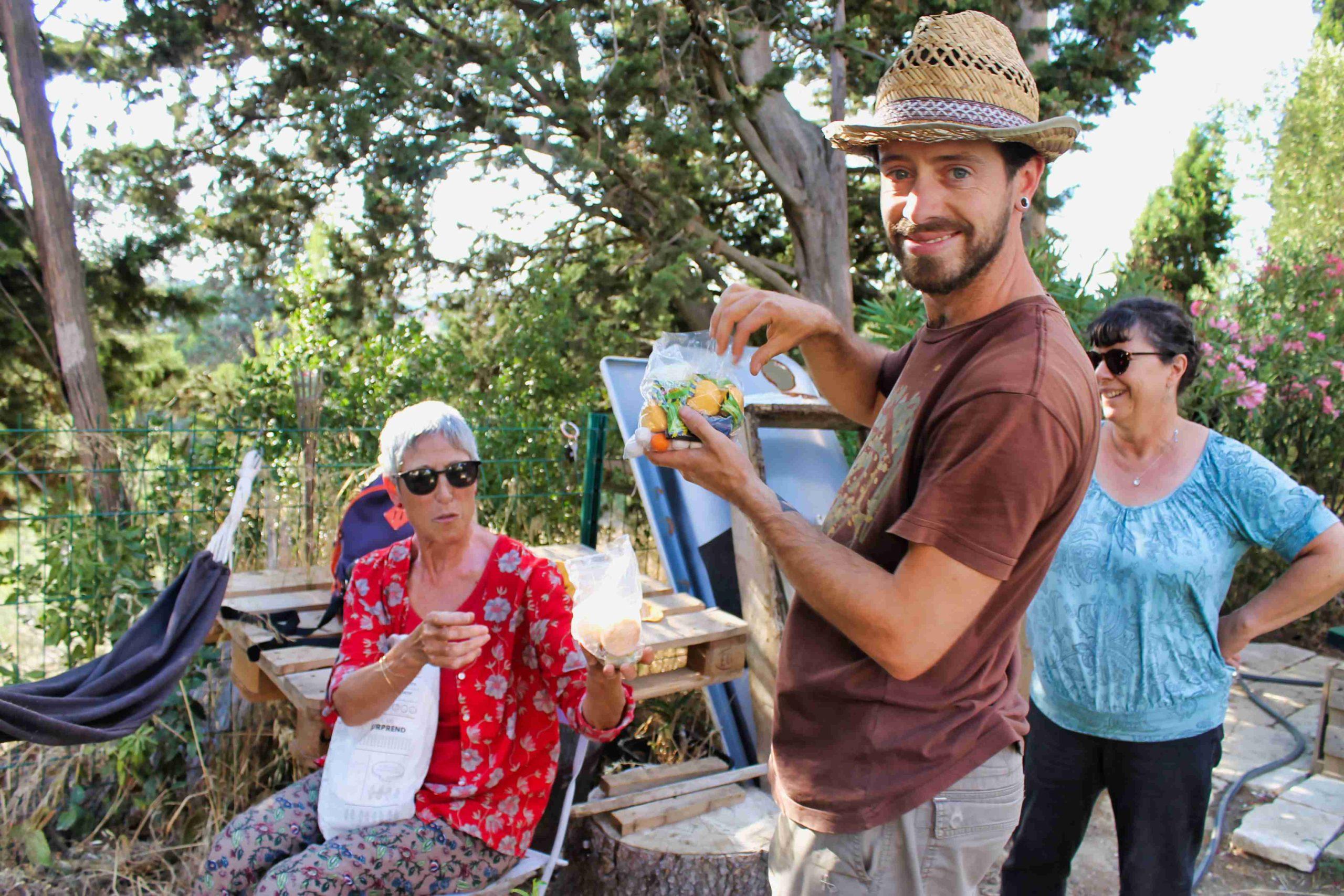 des gens partageant un repas dans un jardin partagée en été, sous un beau soleil de fin d'après-midi