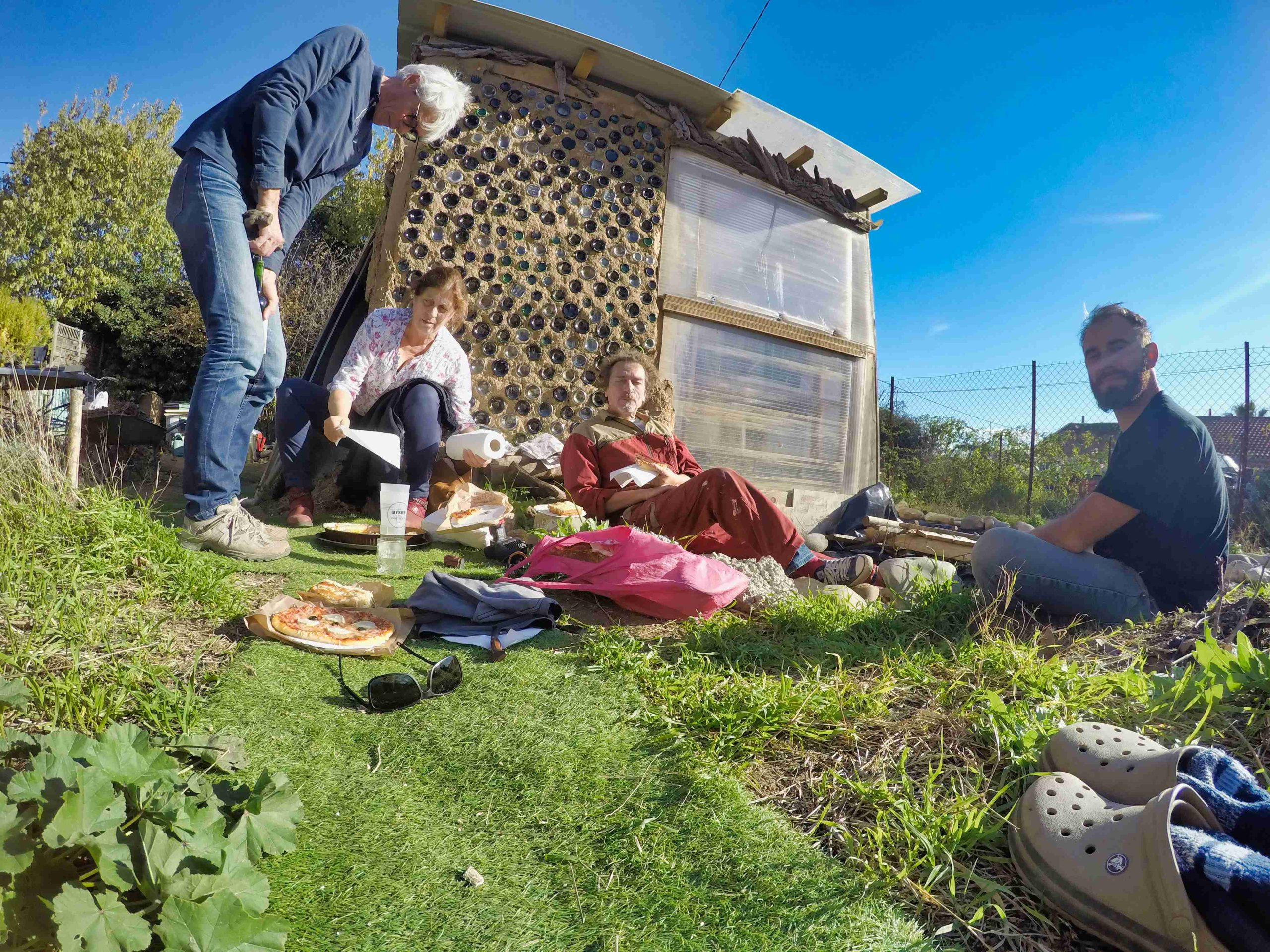 des gens savourant une pause déjeuner devant une serre bioclimatique sous un beau ciel bleu et ensoleillé, dans l'herbe au pied d'un mur en bouteilles de verre.
