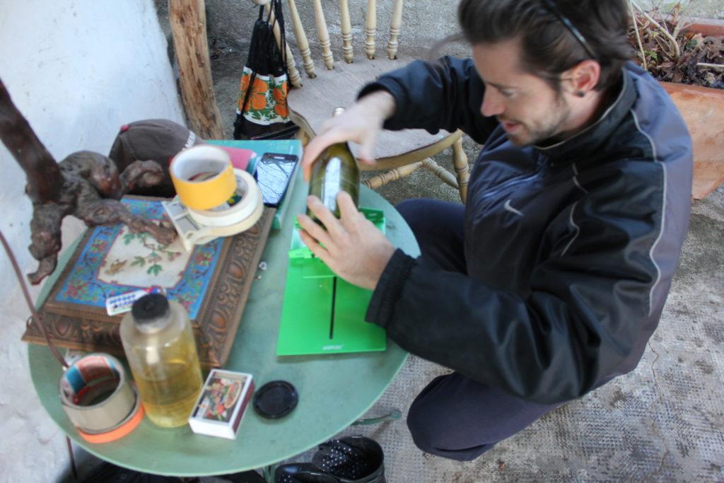 Personne avec une bouteille en verre dans les mains, effectue un tracé avec un diamant.