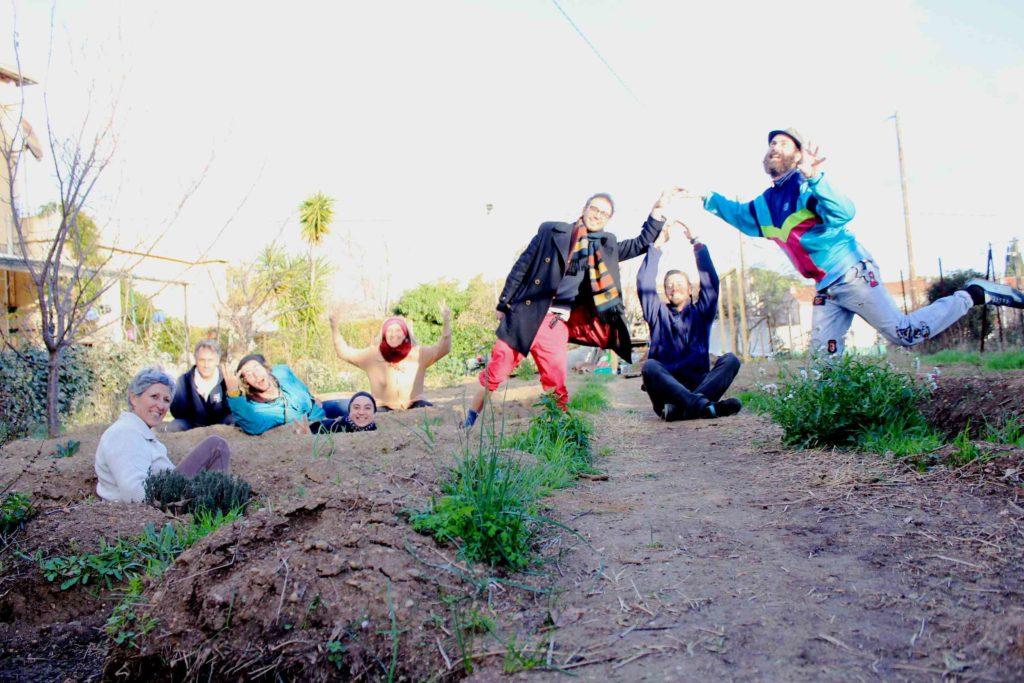 des bénévoles jardiniers posant avec le sourire pour la photographie, dans un jardin partagé, au sol.
