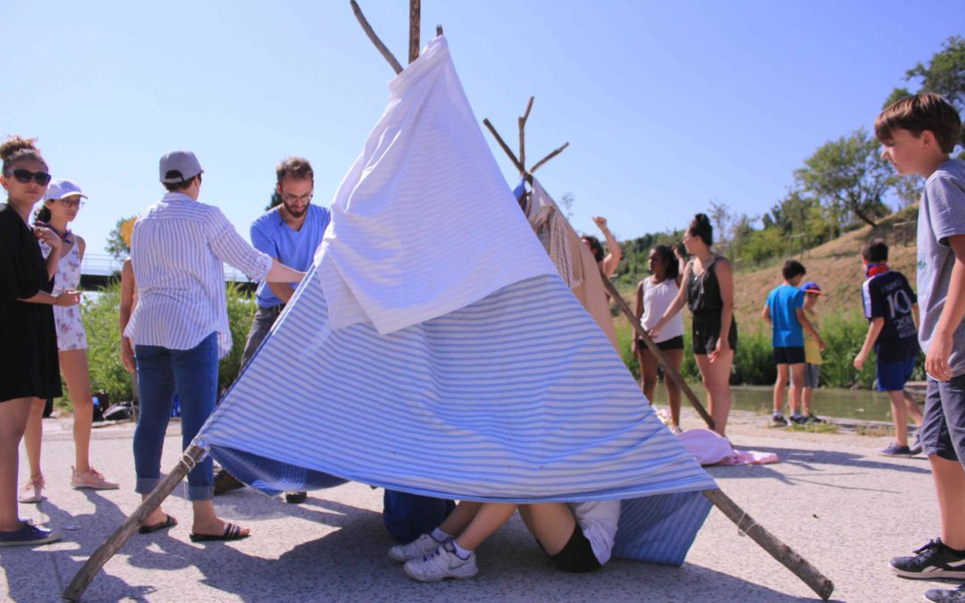 photographie d'un tippi fait par des éclaireurs de france lors d'un atelier natura-lien aux neufs écluses à béziers, la photo montre une quinzaine d'enfants au soleil fabriquant des tippies.