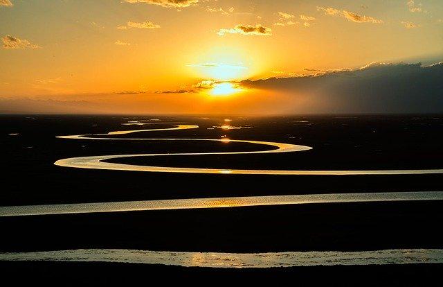 méandre d'une rivière et vue sur un coucher de soleil d'une belle couleur jaune