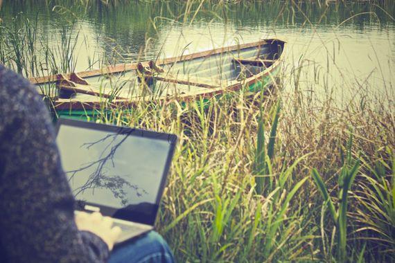 un jardinier dans son jardin, travaillant à la pépinière web de natura-lien, sur un vieil ordinateur